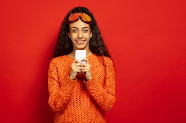 Das porträt der jungen brünettenfrau der afroamerikaner in der skimaske auf rotem studiohintergrund. konzept der menschlichen emotionen, gesichtsausdruck, verkauf, anzeige, wintersport und feiertage. mit dem telefon chatten.