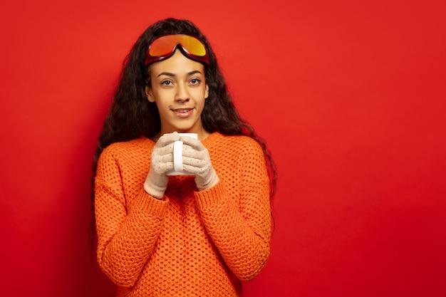 Das porträt der jungen brünettenfrau der afroamerikaner in der skimaske auf rotem studiohintergrund. konzept der menschlichen emotionen, gesichtsausdruck, verkauf, anzeige, wintersport und feiertage. trinkt tee, kaffee.