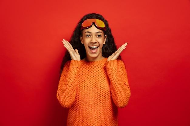 Das porträt der jungen brünettenfrau der afroamerikaner in der skimaske auf rotem studiohintergrund. konzept der menschlichen emotionen, gesichtsausdruck, verkauf, anzeige, wintersport und feiertage. überrascht, erstaunt.