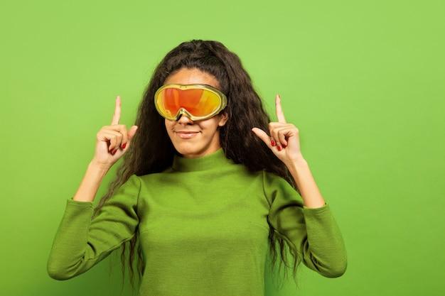 Das porträt der jungen brunettefrau der afroamerikaner in der skimaske auf grünem studiohintergrund. konzept der menschlichen emotionen, gesichtsausdruck, verkauf, anzeige, wintersport und feiertage. lächelnd und nach oben zeigend.