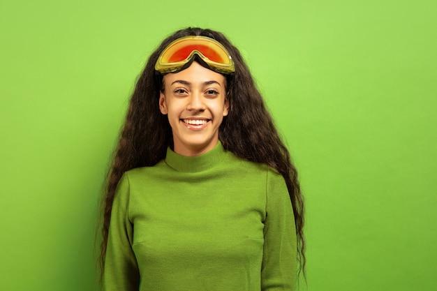 Das porträt der jungen brunettefrau der afroamerikaner in der skimaske auf grünem studiohintergrund. konzept der menschlichen emotionen, gesichtsausdruck, verkauf, anzeige, wintersport und feiertage. lächelt, sieht glücklich aus.
