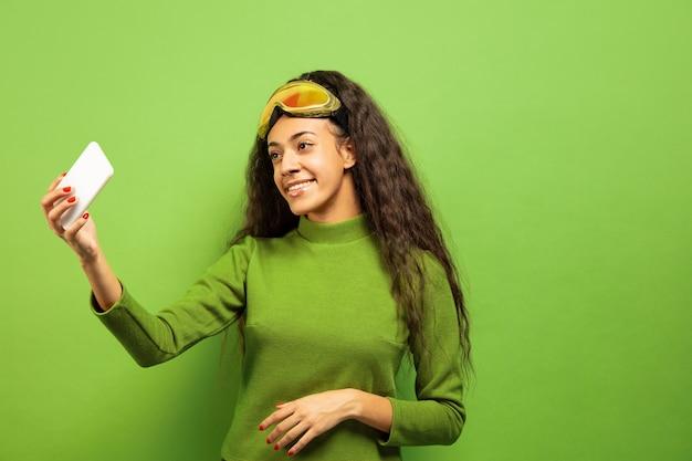 Das porträt der jungen brunettefrau der afroamerikaner in der skimaske auf grünem studiohintergrund. konzept der menschlichen emotionen, gesichtsausdruck, verkauf, anzeige, wintersport und feiertage. selfie oder vlog machen.