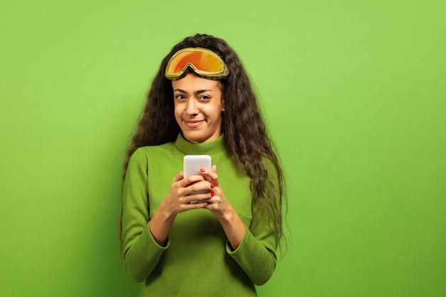Das porträt der jungen brunettefrau der afroamerikaner in der skimaske auf grünem studiohintergrund. konzept der menschlichen emotionen, gesichtsausdruck, verkauf, anzeige, wintersport und feiertage. smartphone benutzen.