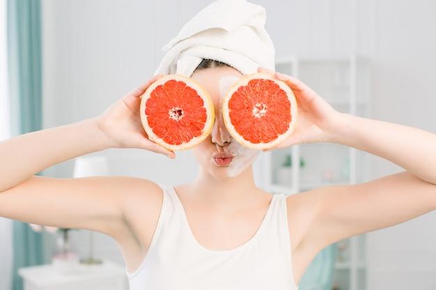 Das porträt der jungen glücklichen schönen frau mit der gesunden, vollkommen glatten haut hält zwei grapefruitstücke und schließt zwei augen. naturkosmetik, hautpflege, wellness, gesichtsbehandlung, kosmetikkonzept.