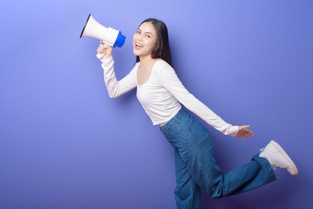 Das porträt der jungen schönen lächelnden frau verwendet megaphon, um über isoliertem purpur anzukündigen