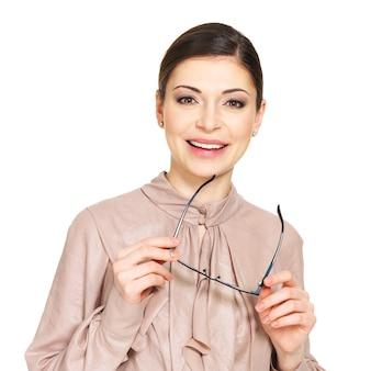 Das porträt der schönen glücklichen jungen frau im beige hemd hält die brille lokalisiert auf weißem hintergrund