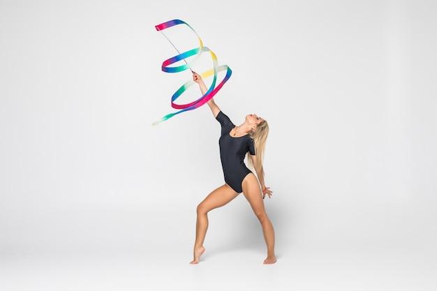 Das porträt der schönen jungen frau turnerin training calilisthenics übung mit band. kunstgymnastikkonzept.