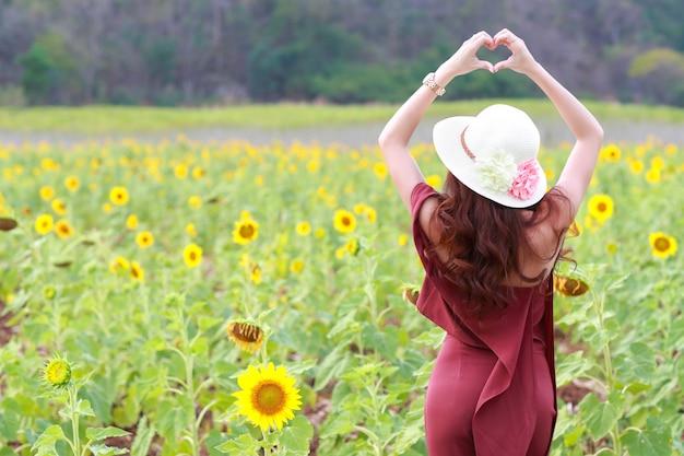 Das porträt der schönheit eine glückliche zeit habend und tun herzsymbol im sonnenblumenfeld in der natur