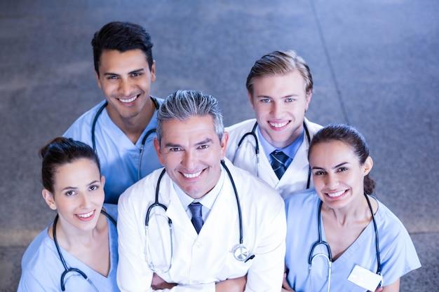 Das porträt des ärzteteams stehend mit den armen kreuzte im krankenhaus