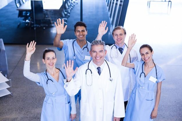 Das porträt des ärzteteams stehend mit ihrer hand hob in krankenhaus an