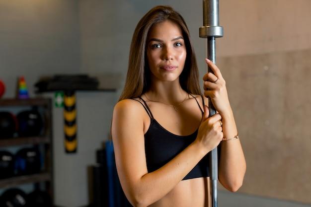 Das porträt des athleten in einem schwarzen oberteil mit braunen haaren, das im fitnessstudio steht und eine metallhantel hält, schaut direkt in die kamera