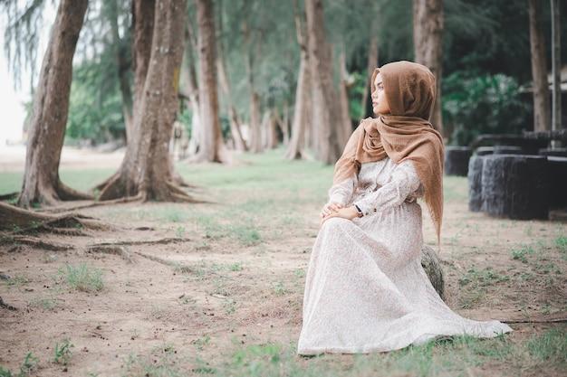 Das porträt des braunen hijab der jungen muslimischen frau über verwischte den kiefernwald