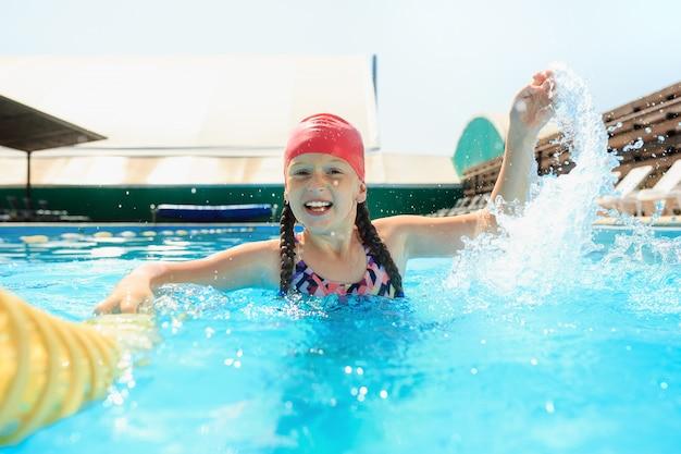 Das porträt des glücklichen lächelnden schönen jugendlich mädchens am pool