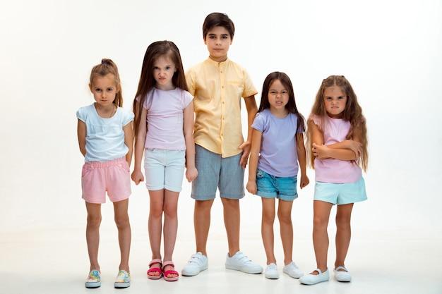 Das porträt des glücklichen niedlichen kleinen kinderjungen und der mädchen in der stilvollen freizeitkleidung, die kamera gegen weiße wand betrachtet