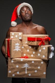 Das porträt des gutaussehenden jungen schwarzafrikaners überraschte den mann in der weihnachtsmütze mit geschenken auf dunklem hintergrund. positive menschliche emotionen und frohe weihnachten-konzept