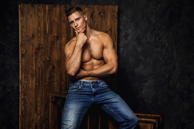 Das porträt des hübschen muskulösen und sexy mannes, der jeans trägt, posiert gegen holzwand
