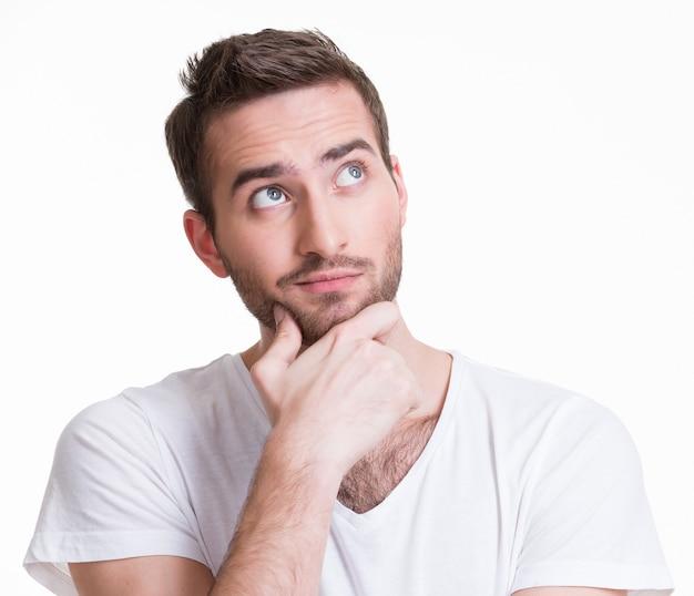 Das porträt des jungen denkenden mannes schaut in den auf weißem hintergrund isolierten casuals nach.