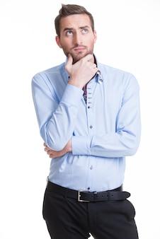 Das porträt des jungen denkenden mannes schaut isoliert in lässig auf