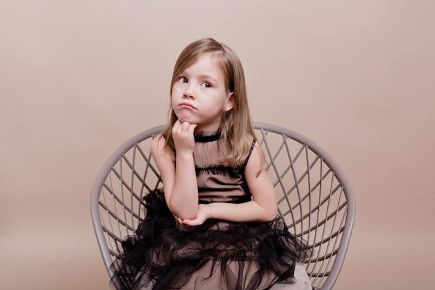 Das porträt des kleinen süßen mädchens trägt ein schwarzes kleid, das auf einem stuhl mit einem nachdenklichen gesicht sitzt und auf einer isolierten wand posiert, echte ernsthafte bewegungen eines hübschen charmanten mädchens
