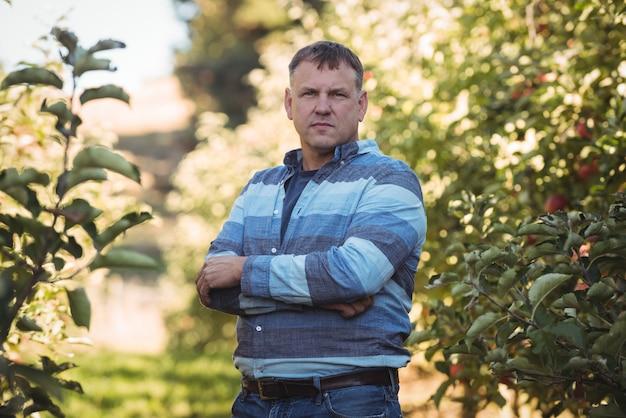Das porträt des landwirts stehend mit den armen kreuzte im apfelgarten