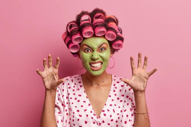 Das porträt des lustigen jungen weiblichen modells beißt die zähne zusammen und hebt die handflächen, zeigt pfoten, gekleidet in einen seidenmantel, macht eine frisur mit lockenwicklern, bekommt schönheitsbehandlungen, bereitet sich auf eine disco-party vor