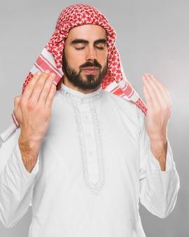 Das porträt des moslemischen mannes betend mit augen schloss