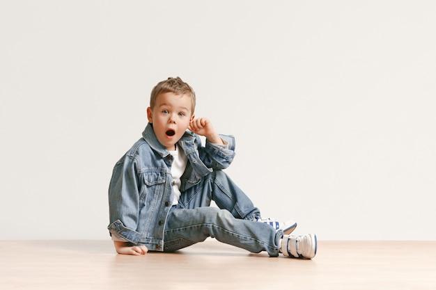 Das porträt des niedlichen kleinen jungen in der stilvollen jeanskleidung, die kamera betrachtet