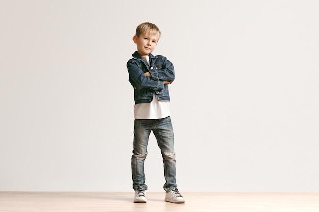 Das porträt des niedlichen kleinen jungen in der stilvollen jeanskleidung, die kamera gegen weiße studiowand betrachtet. kindermode-konzept