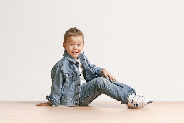 Das porträt des niedlichen kleinen jungen in der stilvollen jeanskleidung, die kamera im studio betrachtet