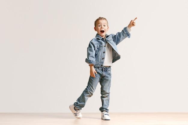 Das porträt des niedlichen kleinen jungen in der stilvollen jeanskleidung