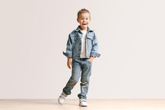 Das porträt des niedlichen kleinen jungen in stilvollen jeans-kleidern, die kamera gegen weiße studiowand betrachten.