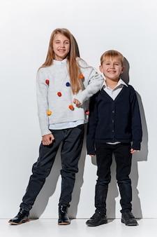 Das porträt des niedlichen kleinen jungen und des mädchens in den stilvollen jeanskleidern, die kamera im studio betrachten