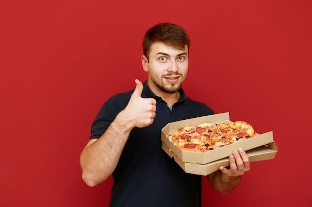 Das porträt des positiven mannes steht und öffnet eine schachtel mit köstlicher frischer pizza