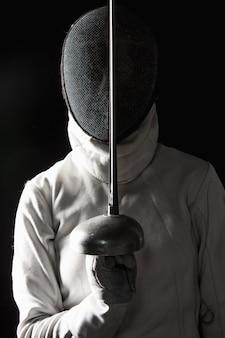 Das porträt des tragenden weißen fechtenkostüms der frau auf schwarzem