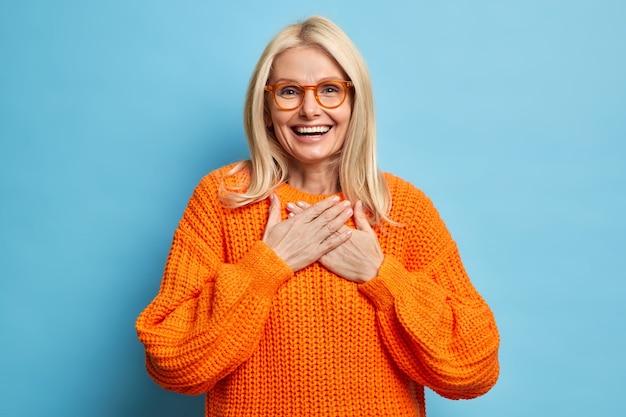 Das porträt einer blonden frau mit fröhlichem ausdruck hält die hände an die brust gedrückt und drückt die dankbarkeit für das herzerwärmende kompliment aus. sie trägt eine brille und einen orangefarbenen pullover.