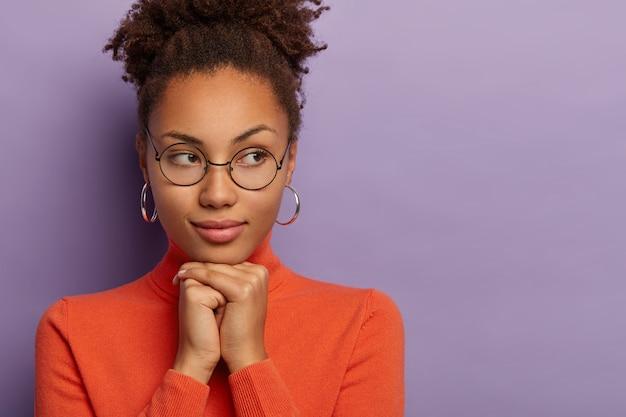 Das porträt einer durchdachten afro-frau hält die hände unter dem kinn zusammen, trägt eine runde brille, ohrringe und einen orangefarbenen rollkragenpullover, der über dem lila hintergrund isoliert ist