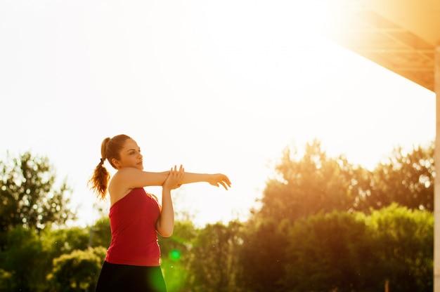 Das porträt einer eignungsfrau, die aufwärmen tut, trainiert draußen