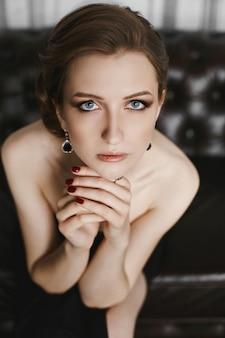 Das porträt einer eleganten und schönen jungen brünetten modelfrau mit sanftem make-up, blauen augen und modischer frisur in einem langen schwarzen kleid sitzt auf dem vintage-sofa im luxus-interieur