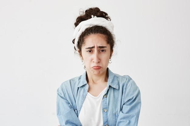 Das porträt einer elenden, düsteren, dunkelhaarigen frau sieht beleidigt aus, runzelt missbilligend die stirn und hört unangenehme kommentare über ihre arbeit. junge frau im jeanshemd von kollegen oder freunden missbraucht