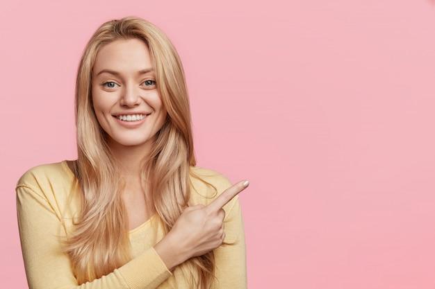 Das porträt einer emotional angenehm aussehenden frau hat ein strahlendes lächeln, das mit dem zeigefinger auf eine leere kopie hinweist und für etwas wirbt. blonde attraktive frau zeigt neues produkt, zieht ihre aufmerksamkeit auf sich