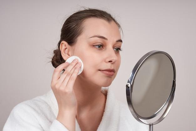 Das porträt einer frau in einem weißen gewand reinigt ihr gesicht mit einem wattepad und schaut in den spiegel. lichtwand.