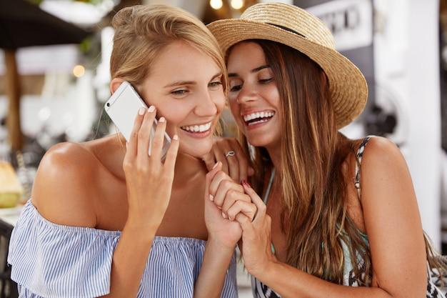 Das porträt einer fröhlichen, entzückenden frau hat ein mobiles gespräch mit einer freundin und ihre eifersüchtige freundin versucht, das gespräch mitzuhören. überglückliche lesben genießen eine gute erholung im café, nutzen moderne technologien