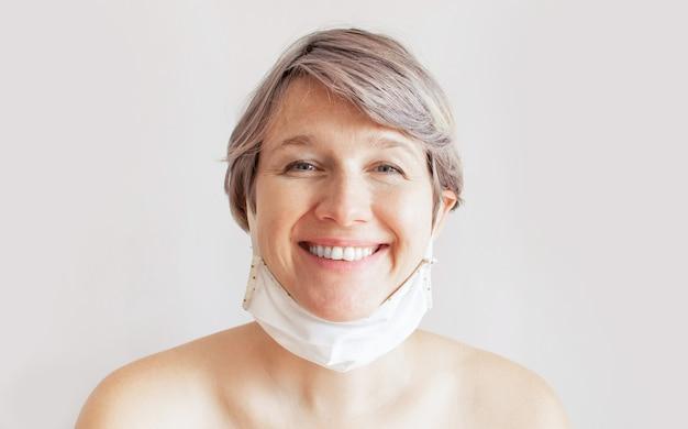 Das porträt einer fröhlichen niedlichen natürlichen frau nahm ihre medizinische schutzmaske ab.