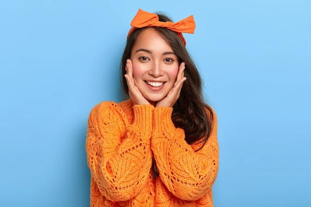 Das porträt einer glücklichen östlichen frau berührt sanft beide wangen, hat ein zartes lächeln, zeigt weiße zähne, trägt ein orangefarbenes stirnband und einen pullover