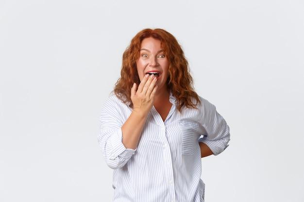 Das porträt einer glücklichen und verblüfften hübschen rothaarigen frau mittleren alters reagiert auf ein amüsantes ereignis und lacht