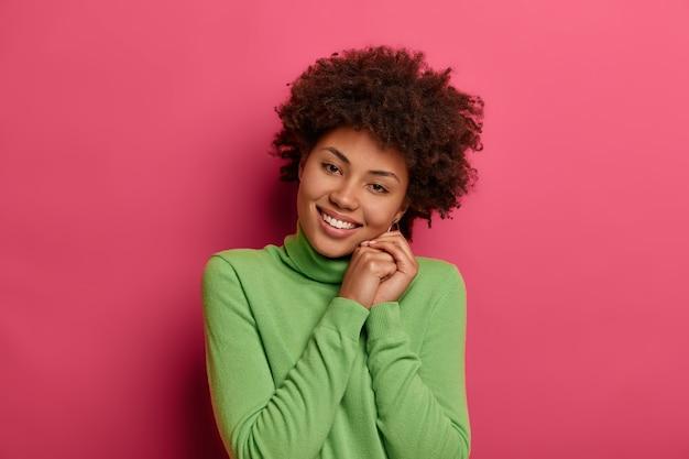 Das porträt einer gut aussehenden lockigen frau neigt den kopf, freut sich, ein wochenende mit ihrer familie zu verbringen, hält die hände zusammen und trägt einen grünen pullover