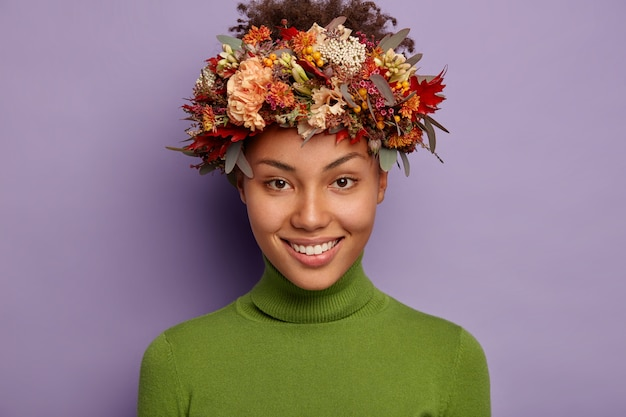 Das porträt einer hübschen dunkelhäutigen frau lächelt angenehm und trägt einen kranz aus herbstblumen
