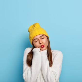 Das porträt einer hübschen frau hält die augen geschlossen und die lippen gerundet, neigt den kopf, mag einen neuen weißen pullover und fühlt sich wohl