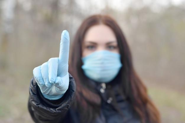 Das porträt einer jungen brünetten frau in blauer schutzmaske und gummihandschuhen zeigt aufmerksamkeitsgeste