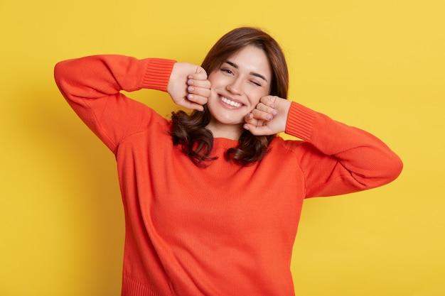 Das porträt einer jungen frau, die sich nach dem schlafen streckt, wacht gerade mit ausgezeichneter stimmung auf, mit einem zahnigen lächeln, einem orangefarbenen freizeitpullover, hält die fäuste auf den wangen.
